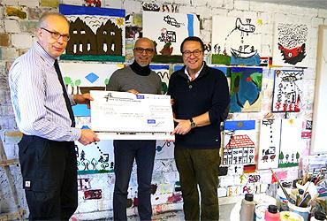 Michael Manthey (l.) überreichte Hasan Deveci und Hans Mörtter einen Scheck für kunstherapeutische Angebote für Flüchtlingskinder