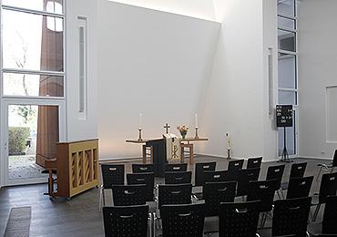 Licht und Bewegung: Die Stirnwand hinter dem Altar neigt sich nach vorn und knickt dann wieder nach hinten ab. Von oben und von den Seiten fällt das Tageslicht ein.