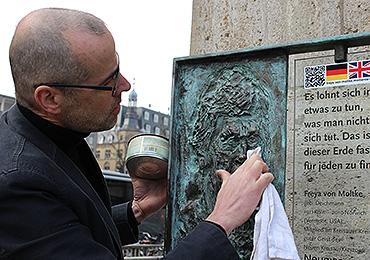 Liebevoll reinigt Christian Bauer das Bronze-Relief der kunstvollen Stele