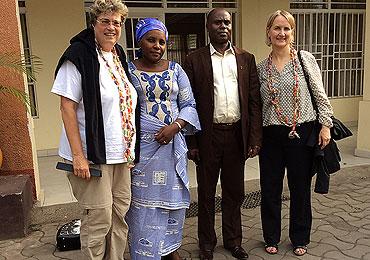 Oberkirchenrätin Barbara Rudolph (l.) und Kirchenrätin Anja Vollendorf (r.) werden am Flufhafen in Goma vom Superintendent und Vorsitzenden der Frauengemeinschaft mit Bonbonketten begrüßt.