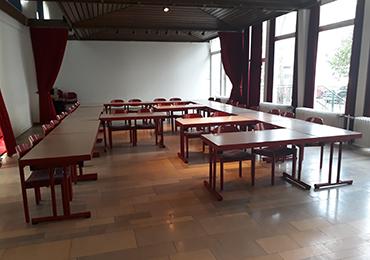 85 stapelbare Stühle mit rot gemusterten Polstern und die dazu passenden 17 zusammenklappbaren Tische mit rotem Holzrand zu verschenken