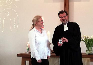 Pfarrer Volker Meiling überreicht Kita-Leiterin Kerstin Besser das Kronenkreuz der Diakonie