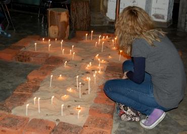 Auch das ist Evangelischer Kirchentag: Während eines Feierabendmahls in leichter Sprache zündet eine Gottesdienstbesucherin in aller Stille eine Kerze an. Foto: Angelika Knapic